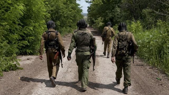 Separatisten in Tarnanzügen laufen eine Strasse entlang.