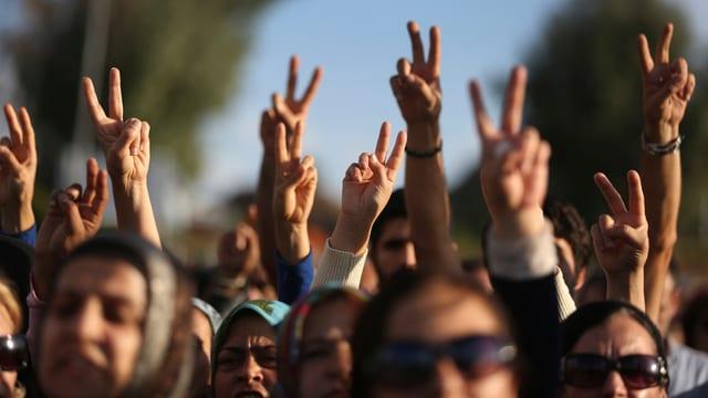 Ein Demonstrationszug in Nahaufnahme, die Menschen strecken ihre Arme hoch und machen mit Zeige- und Mittelfinger das Victory-Zeichen.