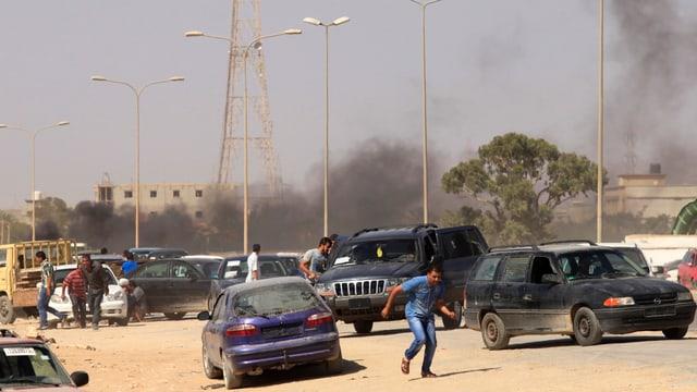 Fahrzeuge und Menschen, im Hintergrund Rauchsäulen