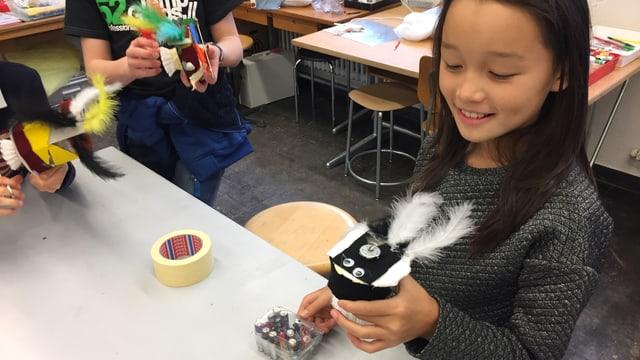 Ein Mädchen hält einen kleinen Roboter mit zwei Federn dran in der Hand.