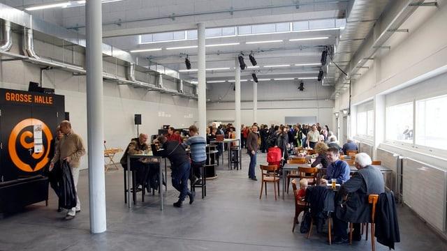 Grosse Halle mit Tischen und Menschen.