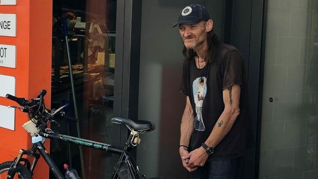 Ein Mann mit Kappe steht vor einer Migros.