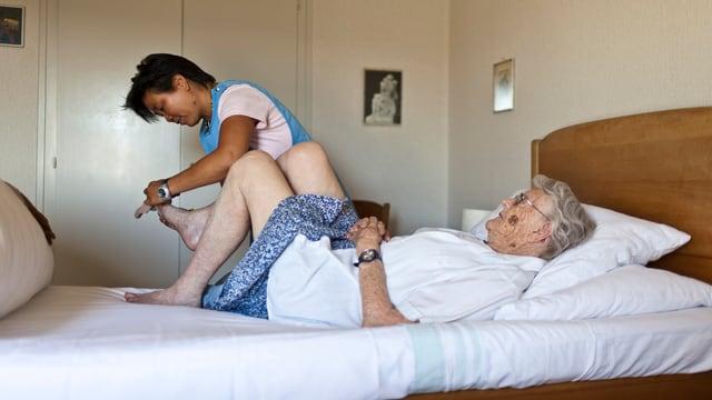 Eine betagte Frau liegt auf dem Bett und lässt sich behandeln.