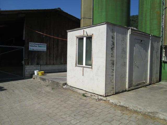 Eine kleine weisse Baracke auf einem Gelände