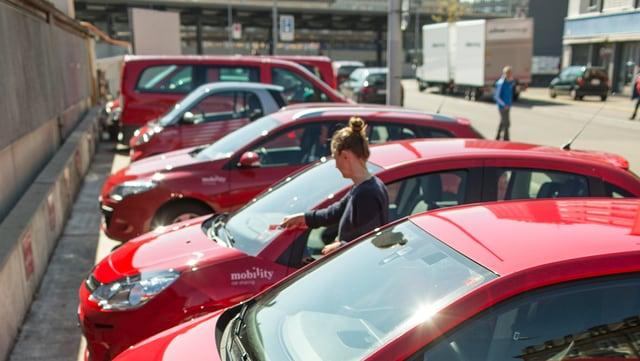 Sechs rote Autos stehen nebeneinander auf einem Parkplatz.