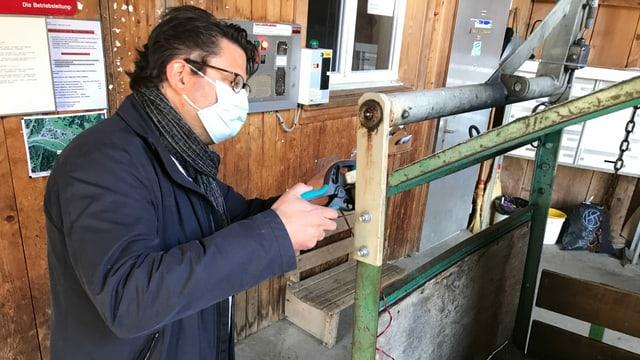 Mann mit Maske mit Zange montiert ein Kabel