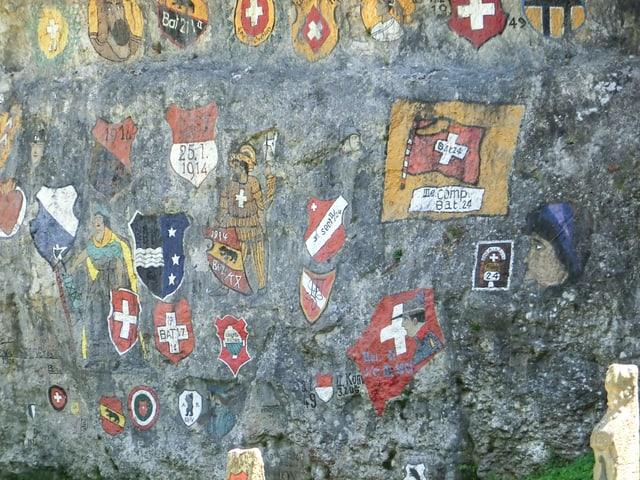 Man sieht eine Felswand mit verschiedenen Schweizer Kantonswappen. Die Wand ist im Chessiloch bei Grellingen.
