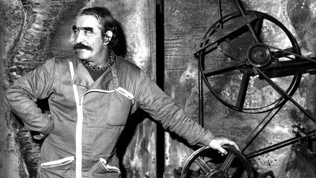 Jean Tinguely steht vor einem Kunstwerk aus Rädern.