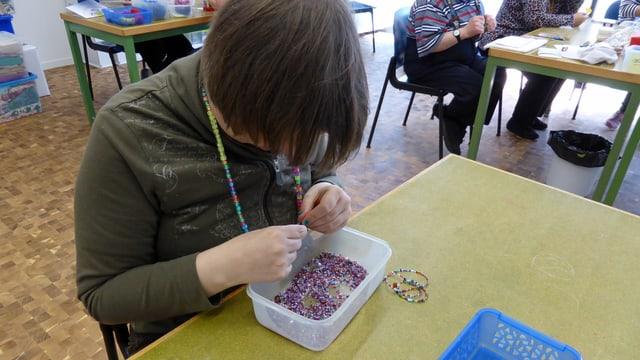 Eine geistig behinderte Frau reiht in den neuen Ateliers der Stiftung Züriwerk Perlen zu Armbändern auf.