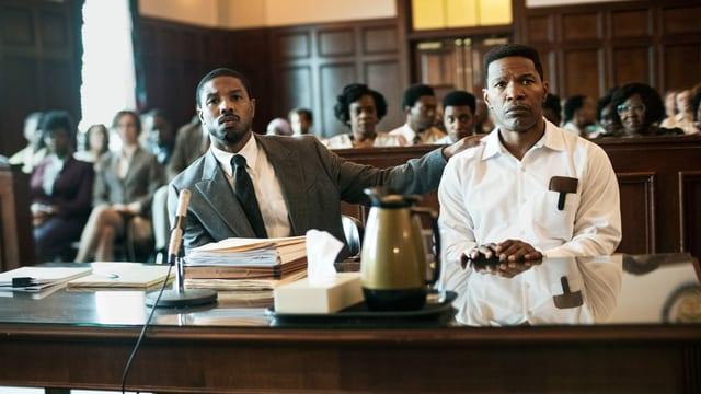 Filmszene: Zwei schwarze Männer sitzen im Gerichtssaal, einer trägt einen Anzug, der andere Sträflingskleidung.