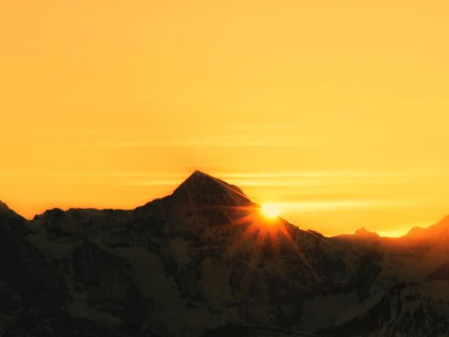 Sonnenaufgang direkt beim Bergkamm. Dahinter gelblicher Himmel.