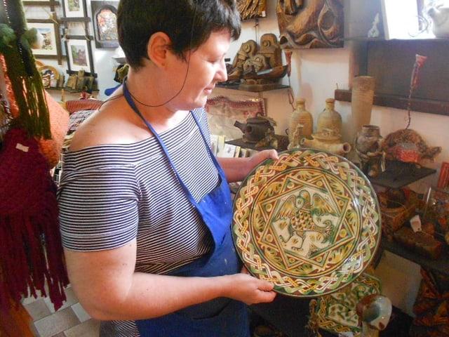 Eine Frau hält einen handbemalten Teller in der Hand.