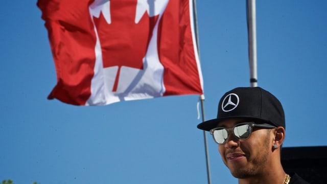 Lewis Hamilton strahlt mit aufgesetzter Sonnenbrille vor der Flagge Kanadas.