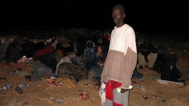 Eine Gruppe Flüchtlinge rastet in der Nacht, im Vordergrund stehend ein Mann.