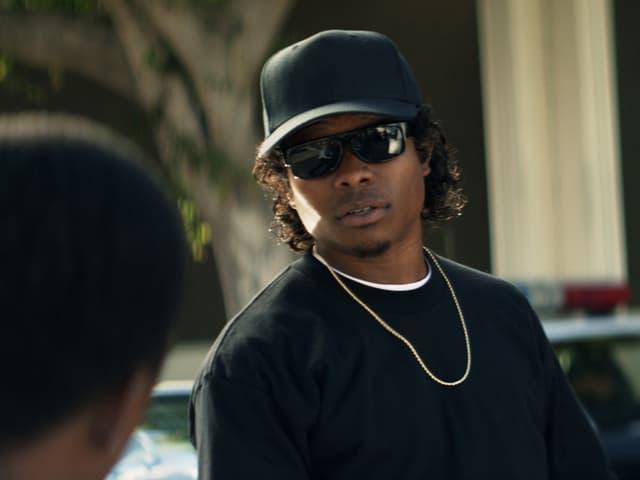 Eazy-E (Jason Mitchell) mit Goldkette, dunklem Cap und schwarzer Sonnenbrille.