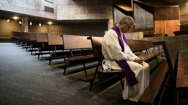 Leere Kirche. Nur ein Pfarrer sitzt in einer Reihe und blickt zu Boden.