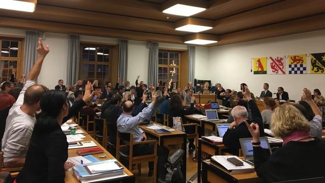 Gemeinderäte stimmen per Handzeichen ab im Parlament.