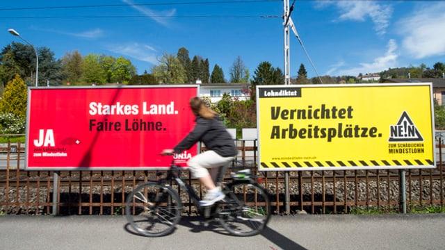 Eine Velofahrerin fährt an zwei Plakaten vorbei