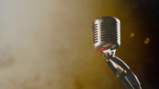 Ein Mikrofon (älteres Modell), dahinter Bühnenlichter und etwas Trockeneis.