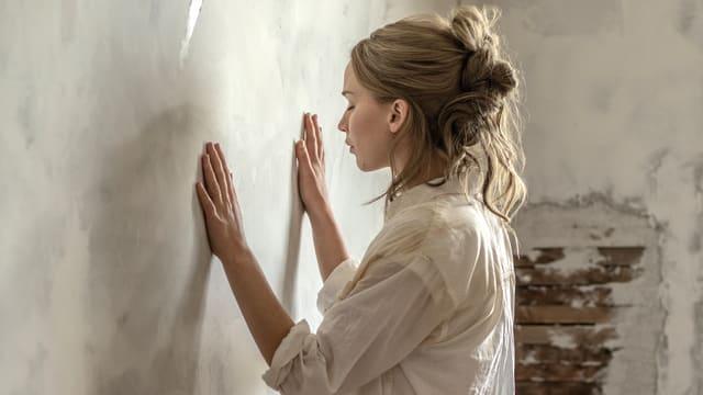 Frau mit geschlossenen Augen hält Hände gegen eine Wand