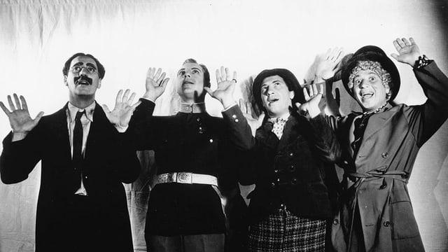 Vier Männer halten ihre Hände in die Luft.