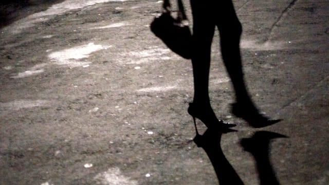 Auf einer dunklen Strasse ist der Schatten von Beinen auf Stöckelschuhen und der dazugehörige Schatten auf dem Asphalt erkennbar.