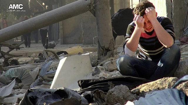 Ein verzweifelter Mann sitzt auf Trümmern eines Hauses in Aleppo.