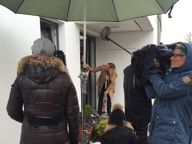 Kamera- und Tontechniker Filmen zwei Frauen an einer Haustür.