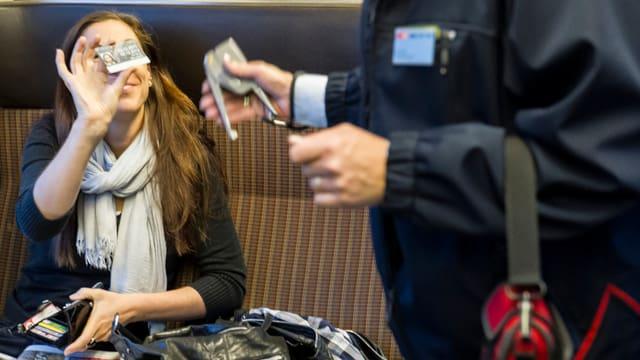 Eine Frau zeigt dem Zugbegleiter das GA.
