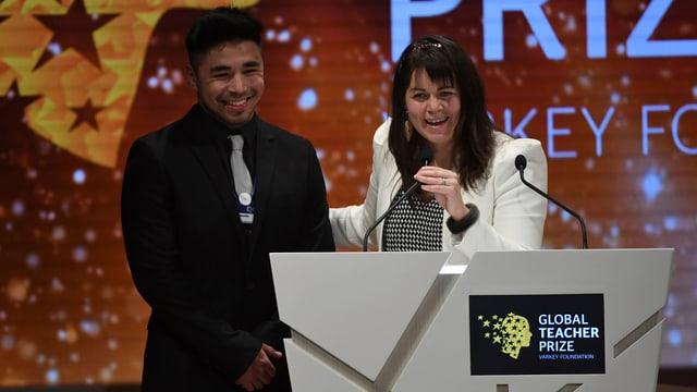 Eine Frau und ein junger Mann hinter einem Rednerpult.