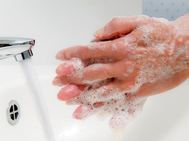 Hände voller Seife vor Wasserhahn