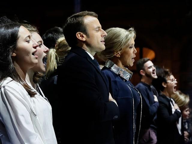 Emmanuel Macron und Brigitte Macron singend.