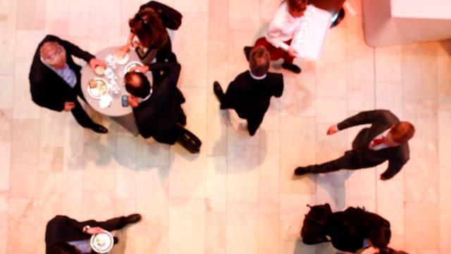 WEF-Teilnehmer von oben in einem Gang gehend und an einem Tischlein stehend.