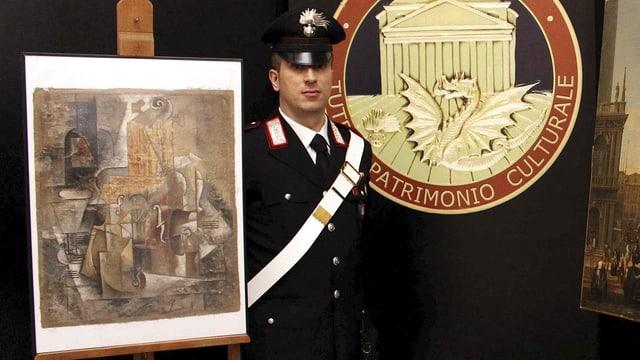 Ein Carabinieri steht neben einem Bild.