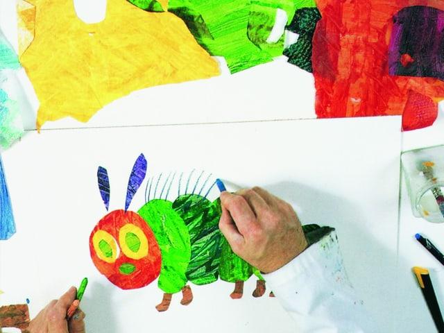 Hände auf einem Schreibtisch, auf dem farbiges ausgeschnittenes Papier und eine Skizze einer Raupe liegen.