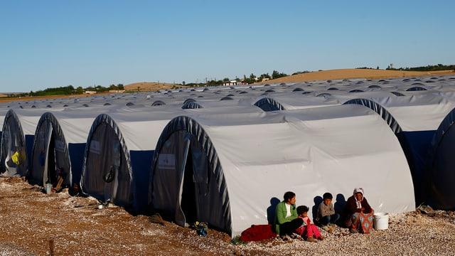 Zeltlager unter blauem Himmel, im Vordergrund sitzen einige Frauen und Kinder an der Sonne.
