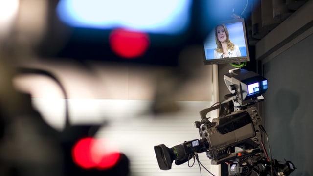 Ein Aufnahmestudio: Auf einem Bildschirm ist das Gesicht einer Moderatorin zu sehen.