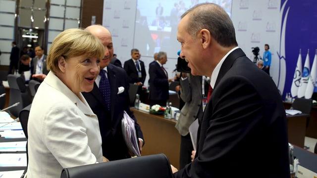 Angla Merkel (links) schüttelt Recep Tayyip Erdogan (rechts) lachend die Hand.