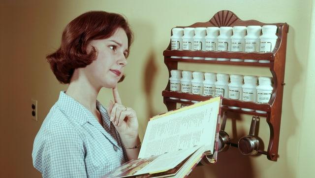 Eine Aufnahme aus den 50er-Jahren zeigt eine Hausfrau vor einem Kräuterregal.