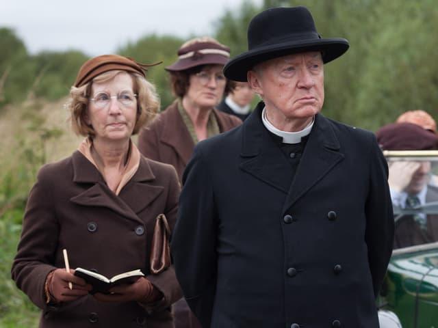 Pfarrer mit Mantel und schwarzem Hut und ernstem Blick. Neben im eine Gruppe Frauen.