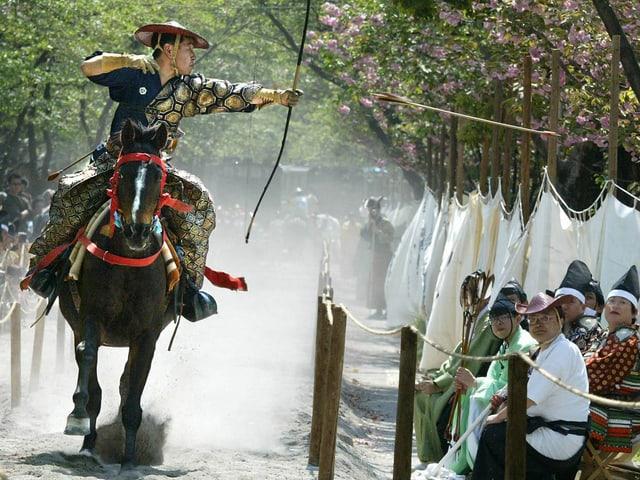 Japanischer Reiter schiesst Pfeil ab. Publikum schaut zu.