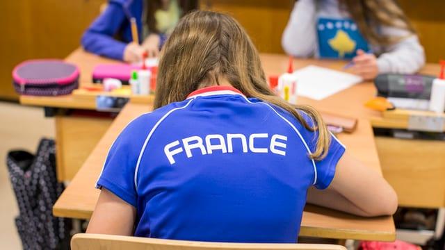 scolar cun in t-shirt che ha scrit «France»