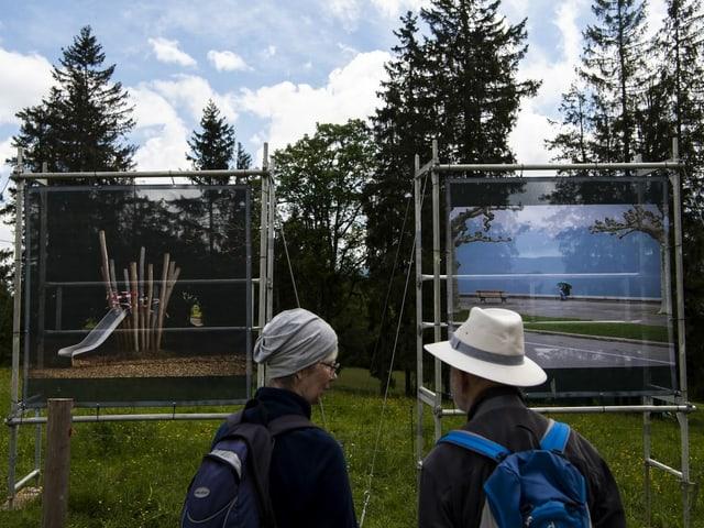 Zwei Personen betrachten Fotografien, die auf einer Wiese aufgestellt wurden.