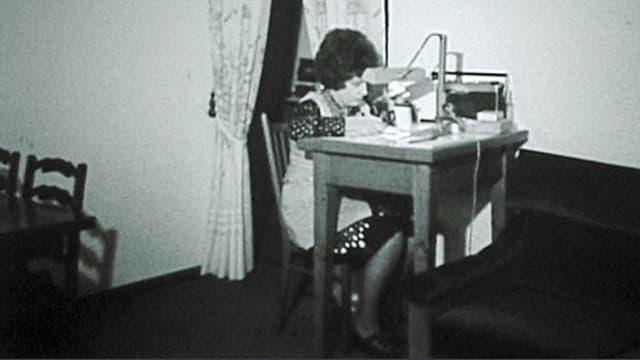 Schwarz-weiss-Aufnahme einer Arbeiterin an einem Tischchen.