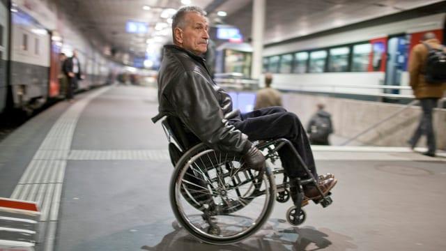 In um en sutga cun rodas davant in tren sin in perrun en ina gronda staziun.