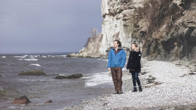 Ein paar steht an einem Steinstrand, hinter ihnen eine steile Felsküste.