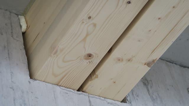 Holzbalen verschwinden in die Betonmauer.