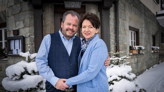 eine Frau und ein Mann stehen vor einem Hoteleingang im Schnee