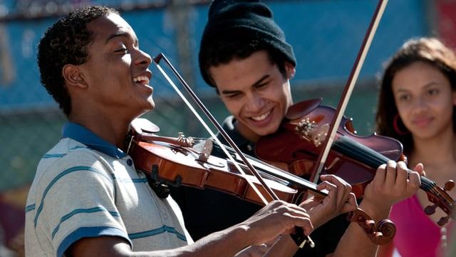 Zwei jugendliche Brasilianer spielen lachend Geige.