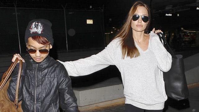 Maddox mit schwarzer Lederjacke und Sonnenbrille läuft neben seiner Mutter Angelina Jolie, die einen weissen Pullover trägt.